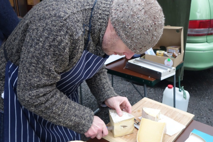 Wrapped up warmly Martin Aspinwall from Canterbury Cheesemongers slices some of the Caerphilly.