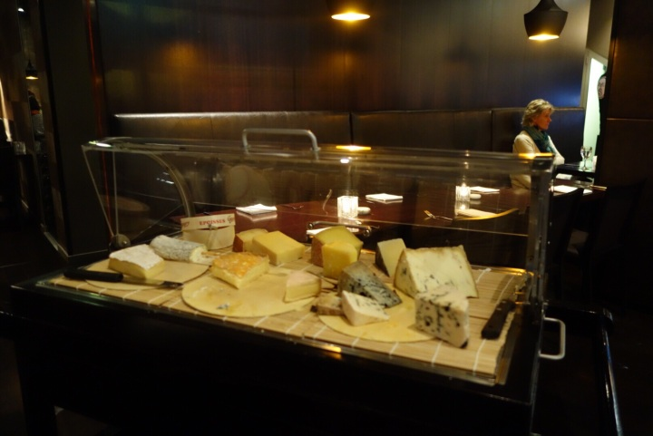 Underneath the glass cover, a treasure trove of cheeses.